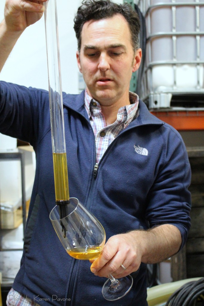 Cidermaker Scott Heath pulls a barrel sample to taste